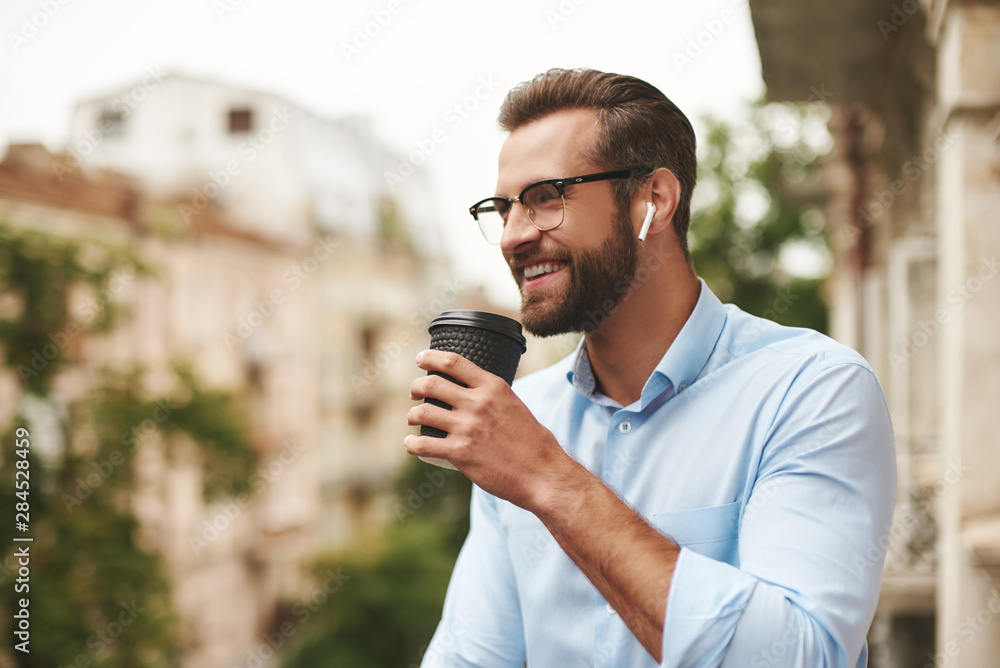 Fototapety, obrazy: Positive news. Young and handsome bearded man in eyeglasses and headphones holding cup of coffee and talking with friend while standing at the office balcony