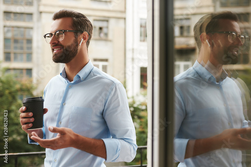 Fototapeta Glad to hear you Portrait of young and handsome bearded man in eyeglasses and he