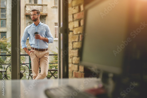 Obraz Having coffee break. Young and handsome bearded man in eyeglasses and formal wear holding cup of coffee and looking away while standing at the office balcony - fototapety do salonu