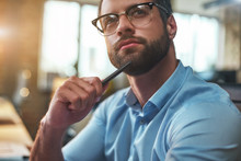 Lost In Thougths. Portrait Of Young Bearded Man In Eyeglasses And Formal Wear Looking Away And Thinking While Working In The Modern Office