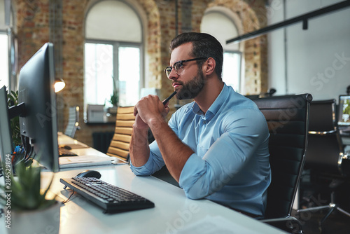 Obraz New ideas. Side view of young bearded man in eyeglasses and formal wear looking at computer and thinking while sitting in the modern office - fototapety do salonu