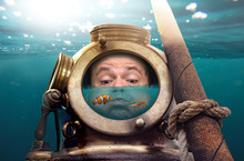 Portrait Of Man In Old Diving Suit And Helmet Under Water. Funny Diver In Retro Equipment With Water And Fish Inside His Helmet .