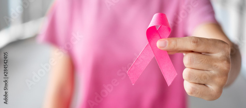 October Breast Cancer Awareness month, Woman in pink T- shirt with hand holding Pink Ribbon for supporting people living and illness. Healthcare, International Women day and World cancer day concept - 284542405