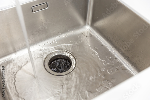 Fotomural  Stainless kitchen sink with food waste disposal in modern home