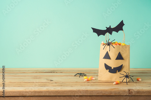 Fototapeta Halloween holiday concept with party gift paper bag decor and candy corn  on wooden table obraz na płótnie