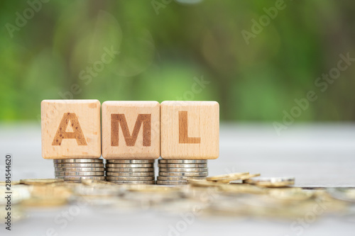 Money laundering concept, wooden word block AML on plie of coins Wallpaper Mural
