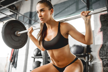 Fototapetastrong sexy athletic young woman working out in gym