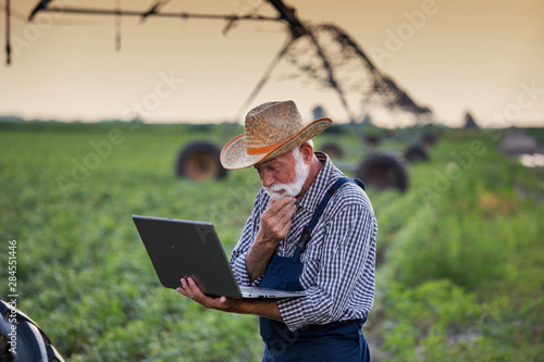 Farmer with laptop in front of irrigation system in field Canvas Print