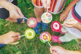 Fototapeta Kawa jest smaczna - Lollipops in the hands of children. Selective focus.