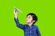 Leinwandbild Motiv Adorable little boy playing a paper plane on studio