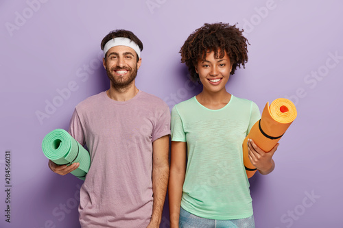 Obraz Indoor shot of happy mixed race female and male ready for fitness training, carry rolled up mats under arms, have glad faces, enjoy active life and everyday regular workout, wear casual sport clothes - fototapety do salonu