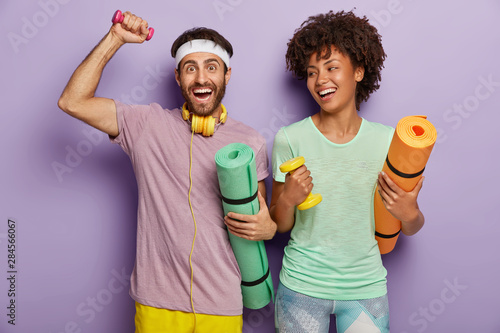 Photo of happy guy and woman work on biceps with weights, carry karemats, have j Tablou Canvas