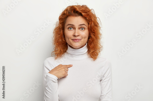 Obraz na plátne Pleasant looking young female points at herself, asks who me, has charming smile, blue eyes, natural red wavy hair, wears white turtleneck, poses against studio background