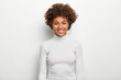 Leinwandbild Motiv Photo of charismatic lovely woman with curly hair, has fun, toothy smile on face, satisfied after successful deal, looks at camera, wears white casual clothes, poses in studio. Happy emotions