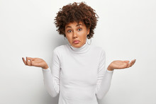 People, Attitude And Life Perception Concept. Clueless Unaware Woman With Curly Hair, Spreads Palms In Doubt, Expresses Uncertainty, Has Hesitant Expression, Wears White Jumper, Shrugs Shoulders
