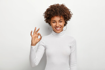 Assertive good looking woman with Afro bushy hairstyle, shows okay gesture, reaffirms choice is excellent, agrees with nice proposal, wears round earrings and white turtleneck, says not bad.