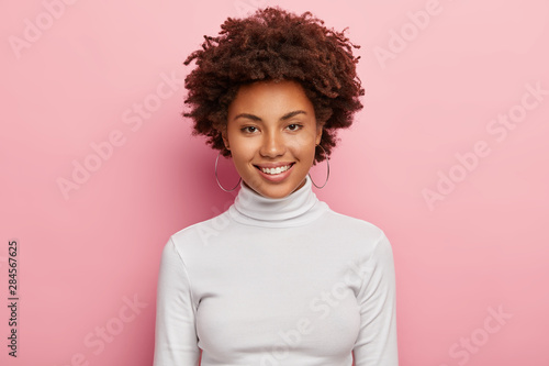 Fotomural  Gorgeous lovely woman has pleasant smile on face, healthy skin, Afro haircut, we