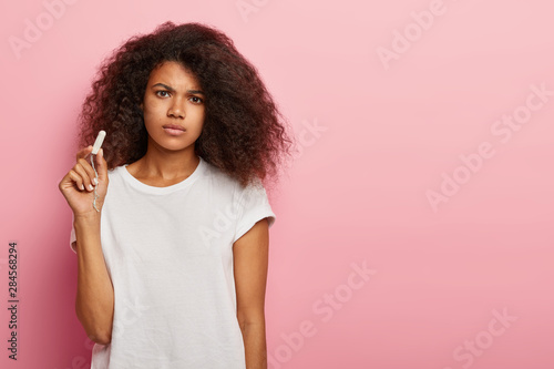 Unhappy curly haired woman holds clean cotton tampon, sad to have menstruation, Wallpaper Mural