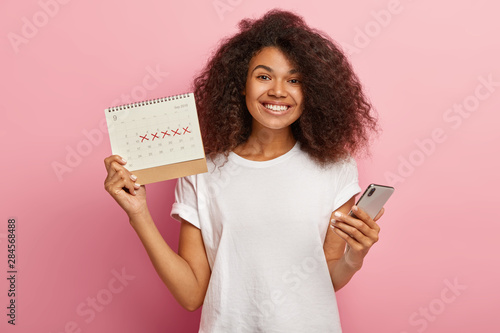 Fotografía Happy curly woman holds periods calendar, checks menstruation days on mobile phone application, cares about women health, dressed casually, isolated on pink studio wall