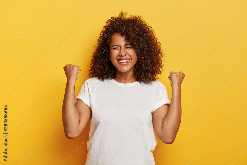 Fototapeta Isolated shot of beautiful successful woman with curly hair, raises clenched fists, celebrates triumph, being very pleased and happy, closes eyes from pleasure, wears white t shirt. Yeah, I did it!