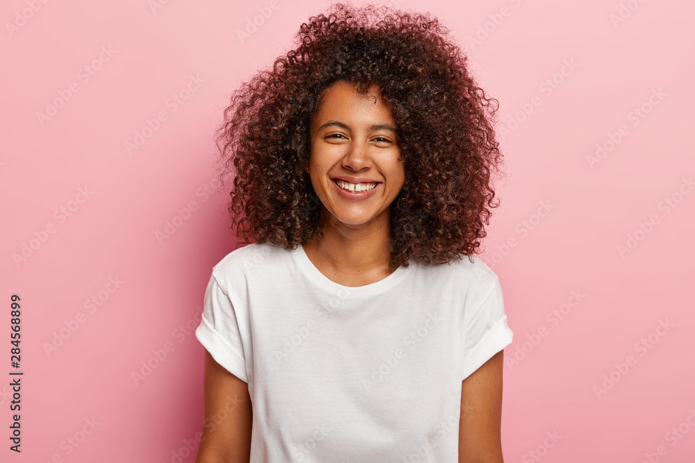 Fototapety, obrazy: Cute happy girlfriend smiles joyfully, has white even teeth, looks at camera, enjoys great time with lover, hears funny joke, wears white t shirt, models against rosy background. Ethnicity concept