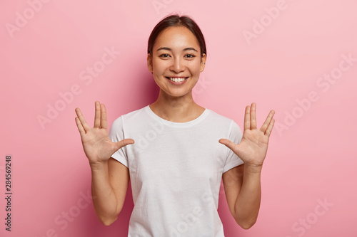 Платно Young Asian female makes vulcan salute hand gesture, keeps arms raised and palms forward with extended thumbs, middle and ring fingers parted, greets you, says live long and prosper