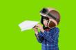 Leinwandbild Motiv Little child wears helmet during play a paper plane
