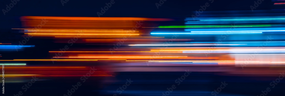 Abstract Rainbow light trails on the dark background