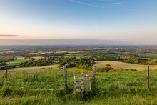 Looking Out Over The Sussex Countryside From Ditchling Beacon, With A Stile In A Fence In The Foreground