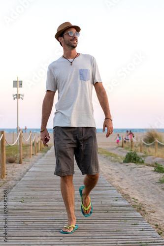 Photo Modelo paseando delante de la playa con sombrero y gafas