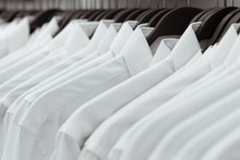 Row Of White Shirts Hang On Bl...