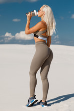 Fitness Woman Drinking Water, Outdoor. Athletic Girl Quenches Thirst. Beautiful Female In Leggings With Sexy Butt
