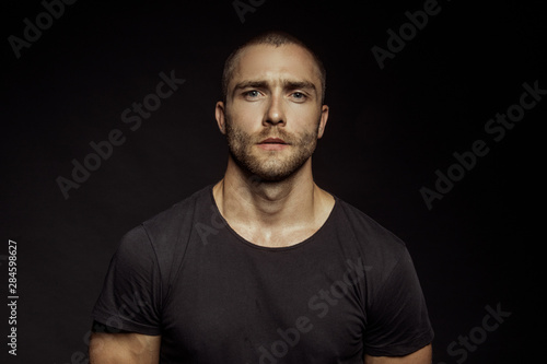 Fotomural  Muscle strong beautiful stripped male model with black t-shirt in denim blue jea