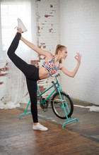 Beautiful Blonde Young Woman (model) In Floral Print Sports Bra Works Out In Industrial Like Gym - Yoga Pose