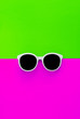 canvas print picture - Sunny stylish white sunglasses on a bright green-cyan and crimson-pink background, top view, isolated. Copy space. Flat lay