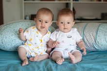 Happy Fraternal Twins Sisters With Pajamas Laughing In Bed At Home.. Family At Home.