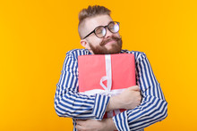 Joyful Young Hipster Guy With A Mustache In Glasses Hugs A Red Gift Box On A Yellow Background. The Concept Of The Joy Of Gifts.