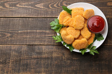 Chicken Nuggets With Red Sauce On A Plate On A Brown Wooden Table. Fast Food. Place For Text. Top View