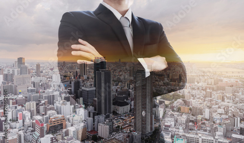 Fotografía  Business leader in black suit with arm crossed, Double exposure city in sunset