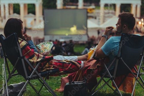 couple sitting in camp-chairs in city park looking movie outdoors at open air ci Fototapeta