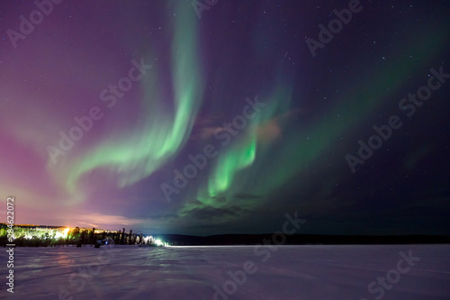 Cadres-photo bureau Aurore polaire Northern shine night sky, bright lights visible on horizon in forest