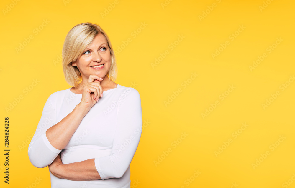 Fototapety, obrazy: Happy smiling beautiful cute lovely blonde senior woman with beauty clean skin in casual wear isolated on yellow background. Healthcare and cosmetology concepts. Pensioner and mature people
