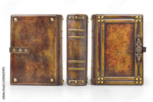 Fotografie, Obraz  Aged large leather book with carved frame, metal pins in the corners, decoration as a door handle and gilded paper edges