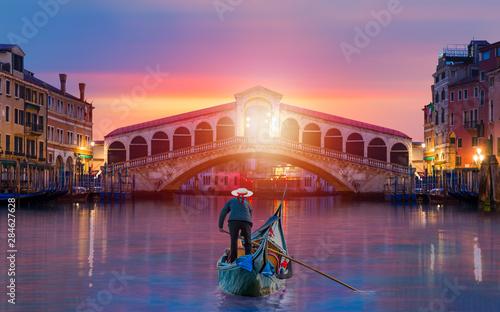 Платно  Gondolier carries tourists on gondola near Rialto Bridge - Venice, Italy