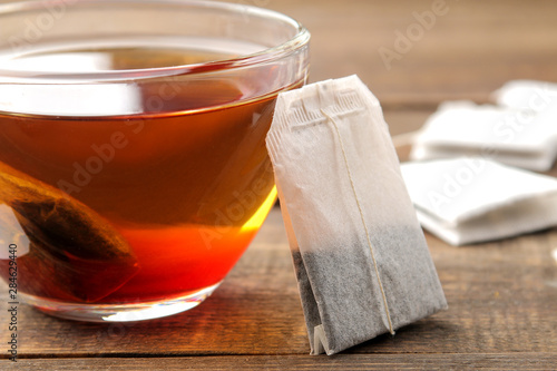 Staande foto Thee Tea bag in a glass cup on a brown wooden background. to make tea