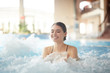 canvas print picture - Portrait of beautiful young woman smiling happily while enjoying bubbly hot tub in SPA, copy space