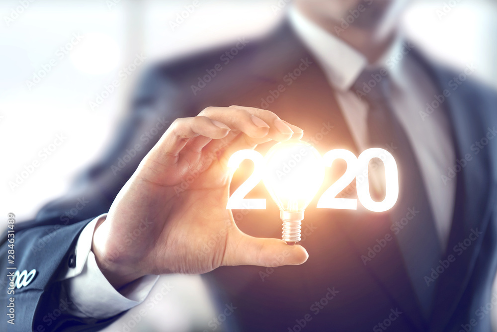 Fototapeta Business idea new year concept, Closeup hand of businessman holding light bulb and number 2020 year.