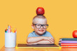 Happy cute clever boy is sitting at desk and smiling. Child is on a yellow background. First time to school. Back to school. pupil in glasses with apple on his head