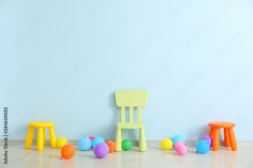 Fototapety, obrazy: Chair, stools and balloons near color wall in children's room
