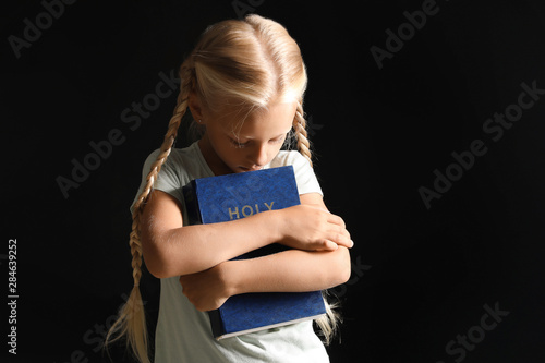 Little girl with Bible on dark background Canvas Print